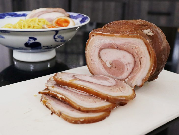 Chashu (Japanese braised pork belly) with bowl of ramen in background