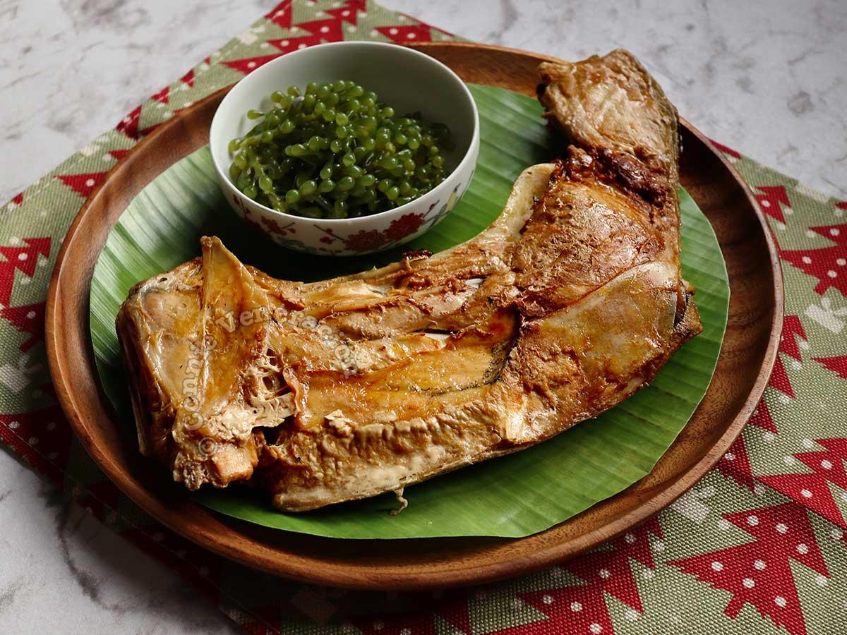 Inihaw na Panga ng Tuna (Grilled Tuna Collar) with lato (sea grapes) on wooden plate lined with banana leaf