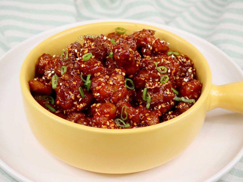 Spicy Korean popcorn chicken garnished with scallions and sesame seeds