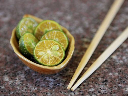Calamansi halves photograpged with chopsticks to show their size