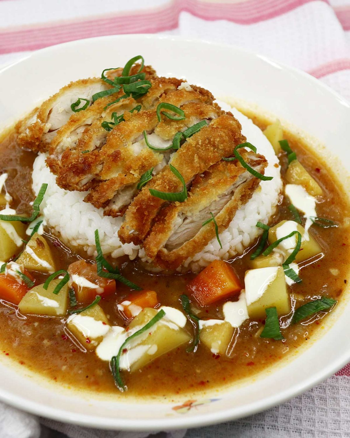 Chicken katsu on rice in a pool of Japanese curry sauce