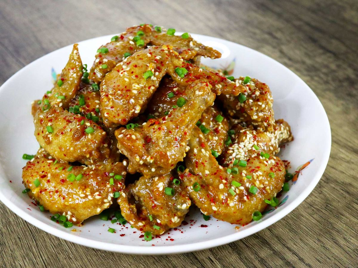 Five-spice Fried Chicken Wings Garnished with Chili Flakes, Scallions and Sesame Seeds