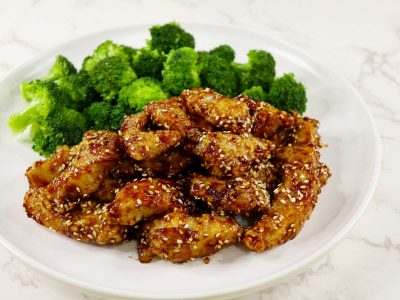 Sesame chicken and blanched broccoli on white Nordic plate