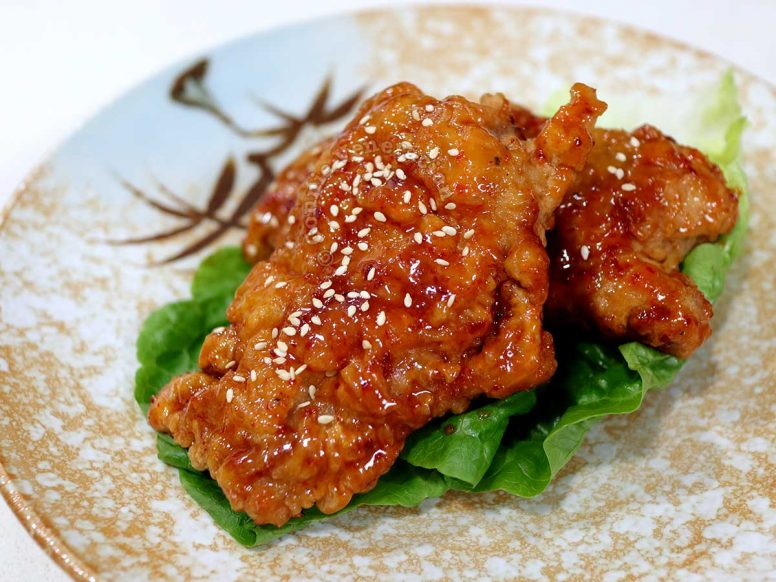 Bonchon-style fried chicken on a bed of lettuce