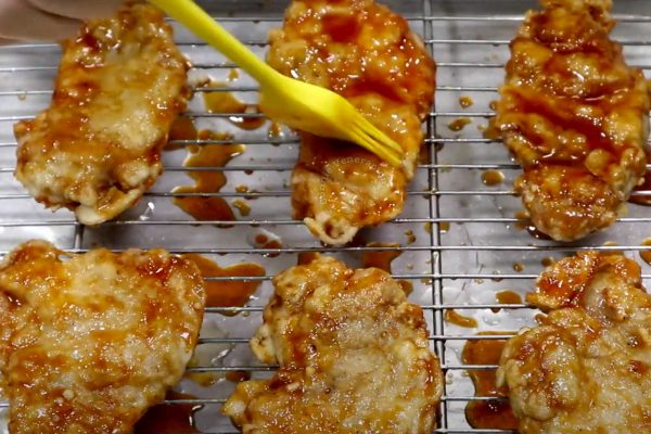 Brushing fried chicken fillets with sauce, Bonchon-style