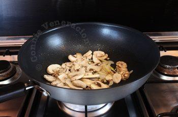 Stir frying sliced mushrooms in wok