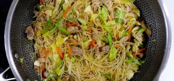 Chicken, vegetables and bee hon (rice vermicelli) stir fry in wok