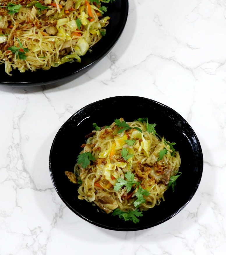Chicken, vegetables and bee hon (rice vermicelli) stir fry in black bowl and black serving plate