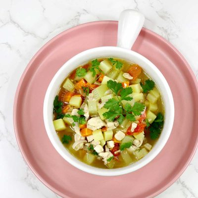 Filipino picadillo soup in whote bowl set on pink plate