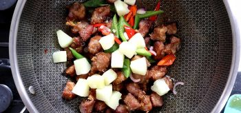 Tossing pork, bell peppers and pineapple in sweet sour sauce