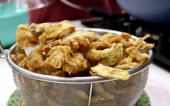 Draining oil off crispy fried oyster mushrooms
