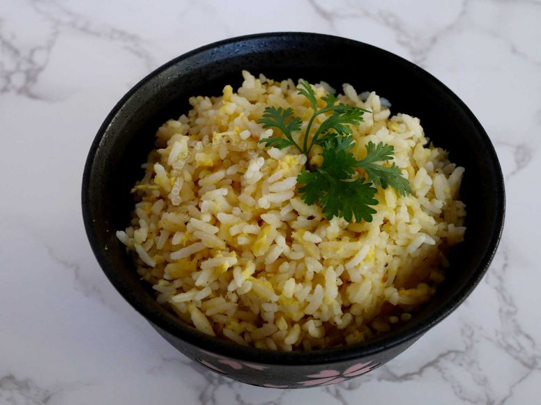 Chinese egg fried rice garnished with a sprig of cilantro