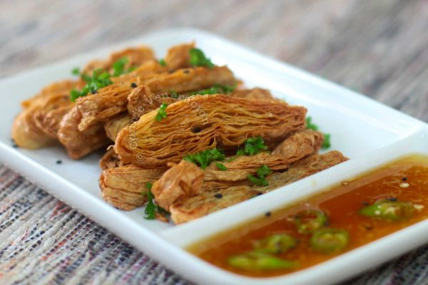 Fried tofu skin sprinkled with chopped parsley and served with sweet chili sauce