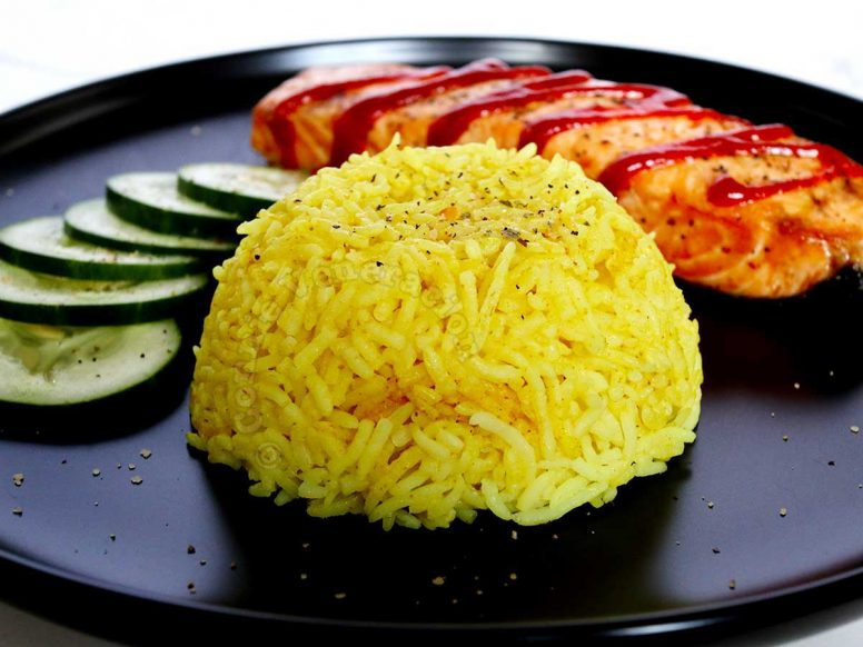 Nasi kuning (Indonesian yellow rice) with salmon and cucumber slices on black plate