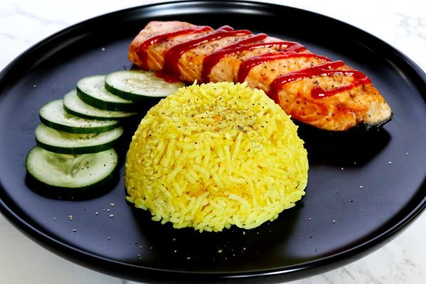Nasi kuning (Indonesian yellow rice) served with pan-fried salmon drizzled with Sriracha