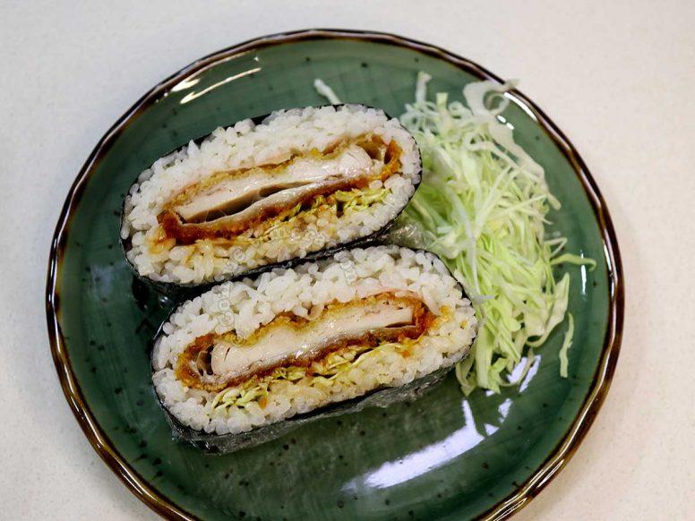 Chicken Tonkatsu Onigirazu (Crispy Chicken and Rice Sandwich) with Shredded Cabbage on a Green Plate