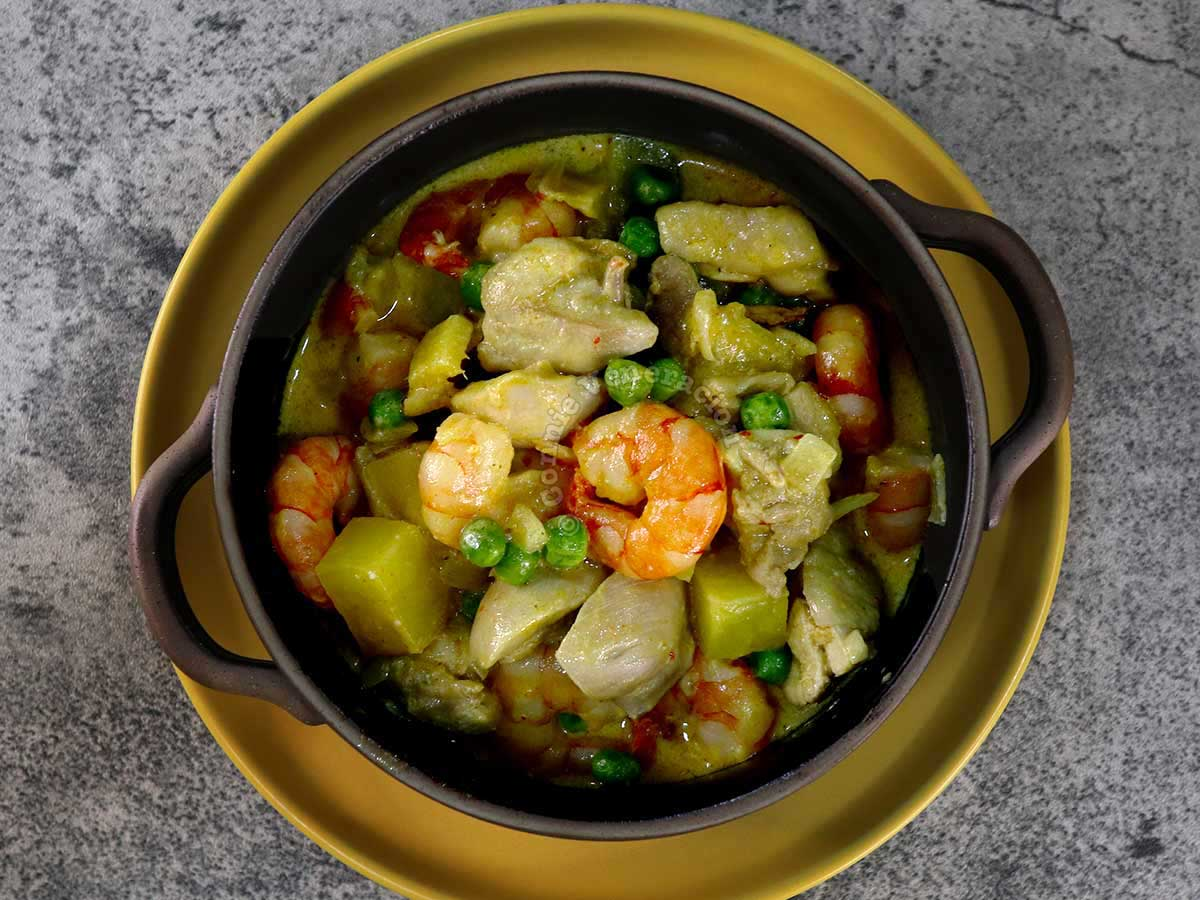 Chicken and shrimp curry in black bowl set over a yellow plate