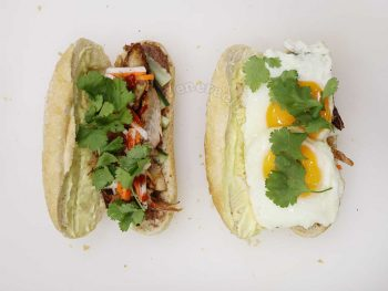 Adding cilantro and fried egg to chicken banh mi