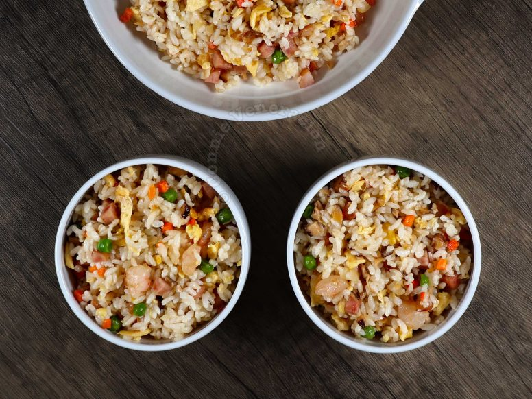 Yang chow fried rice in serving bowl and individual rice bowls