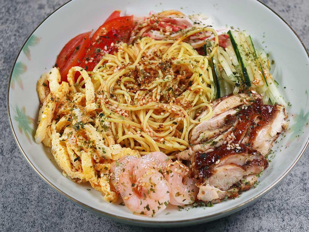 Hiyashi chuka (Japanese cold noodles) with chicken teriyaki, shrimps, cucumber, tomato, eggs and kani
