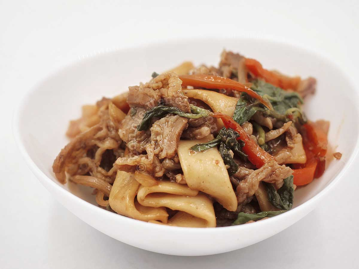 Beef, noodles and vegetables in white bowl