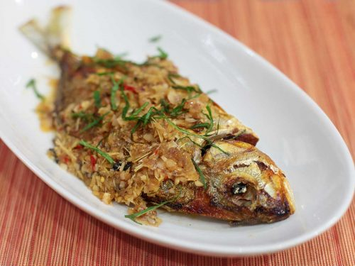 Whole Fish with Lemongrass and Ginger Sauce Garnished with Slivers of Mint Laves