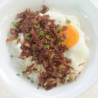 Crispy adobo flakes over rice and egg in white bowl