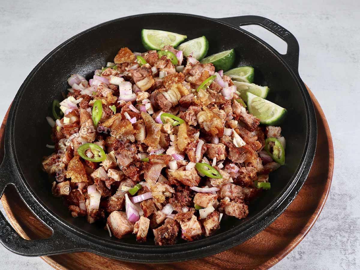 Crispy pork belly sisig in cast iron bowl