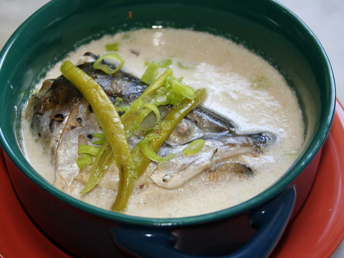 Fish head in coconut milk topped with green chilies and sliced scallions