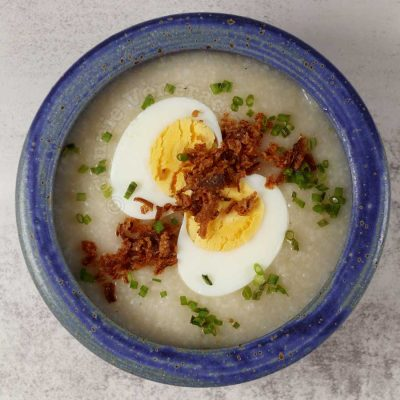 A bowl of congee with halved hard-boiled egg, fried garlic and scallions